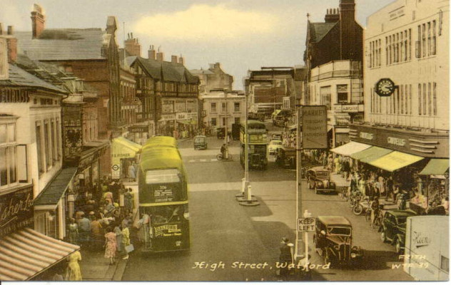 View of Market Place, Cawdells on the right hand side, double decker bus in high street with queue of people waiting to board. | Watford Museum, Frith Series Postcard.