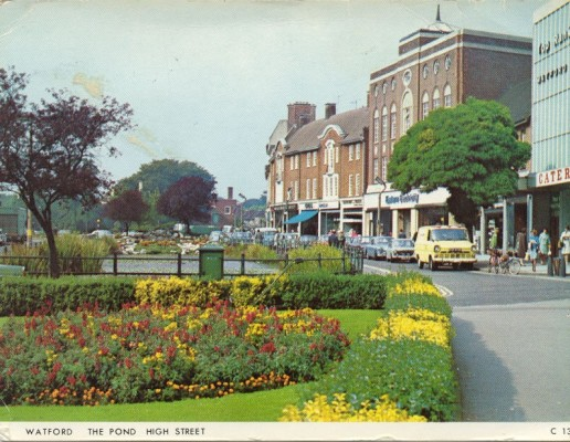 Image of the pond and surrounding garden features. High Street shops to the right, including Top Rank. | Watford Museum