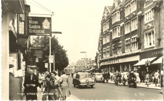 A view of Watford High Street with Clements to the right. Busy with pedestrians.   Watford Museum