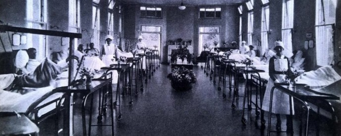 View of the mens ward, beds lined up against the walls and nurses attending to the sick | Peace Hospice